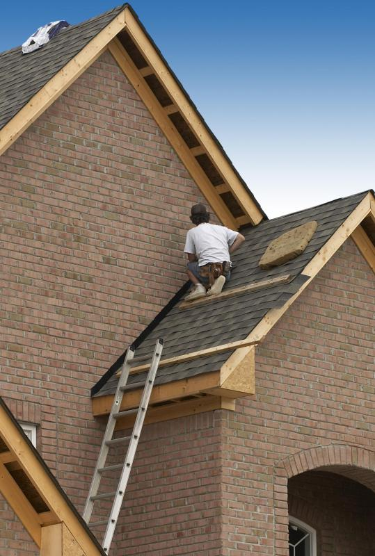 A roofer installing shingles on a house.